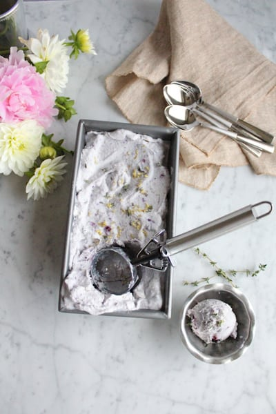 A pan of Blueberry Lemon and Thyme Ice Cream with a scoop of ice cream in a dish.