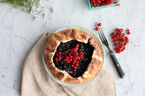 A mini berry galette with napkin and scattered berries and flowers.