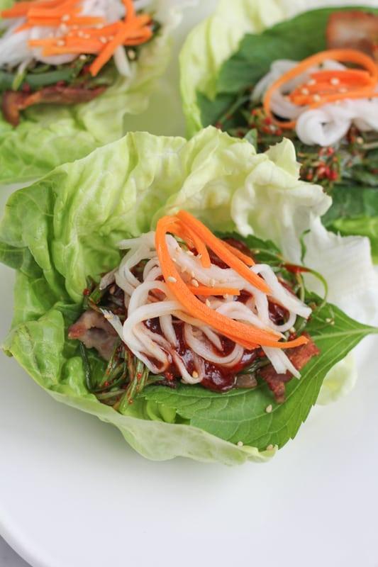 Pork Belly Lettuce Wraps topped with pickled vegetables.