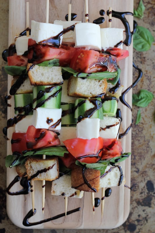 Overhead photo of a stack of caprese kabobs with balsamic glaze on a wood cutting board.