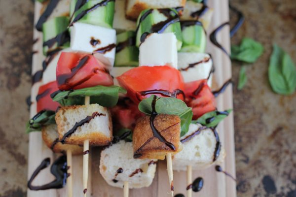 Overhead photo of caprese kabobs with balsamic glaze on a wood cutting board.