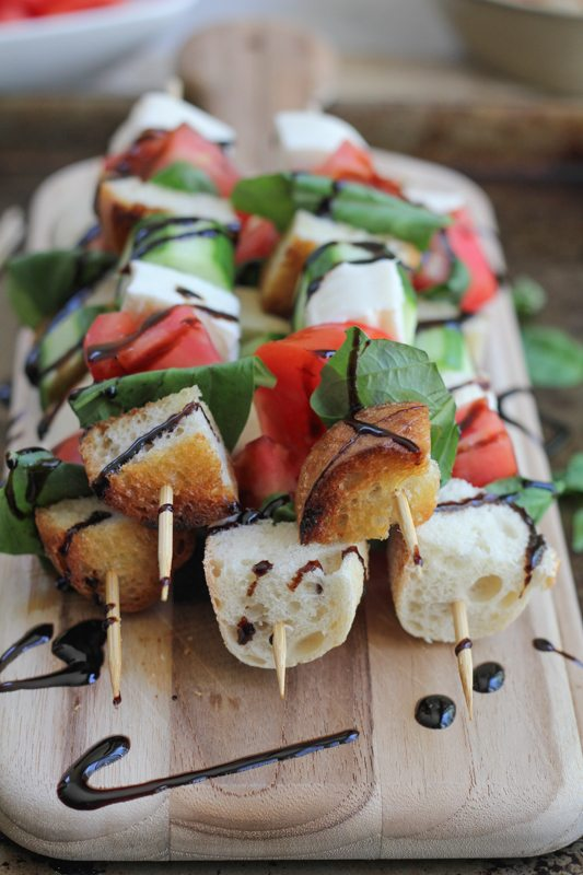 A stack of Caprese kabobs drizzled with balsamic glaze on a wood cutting board.