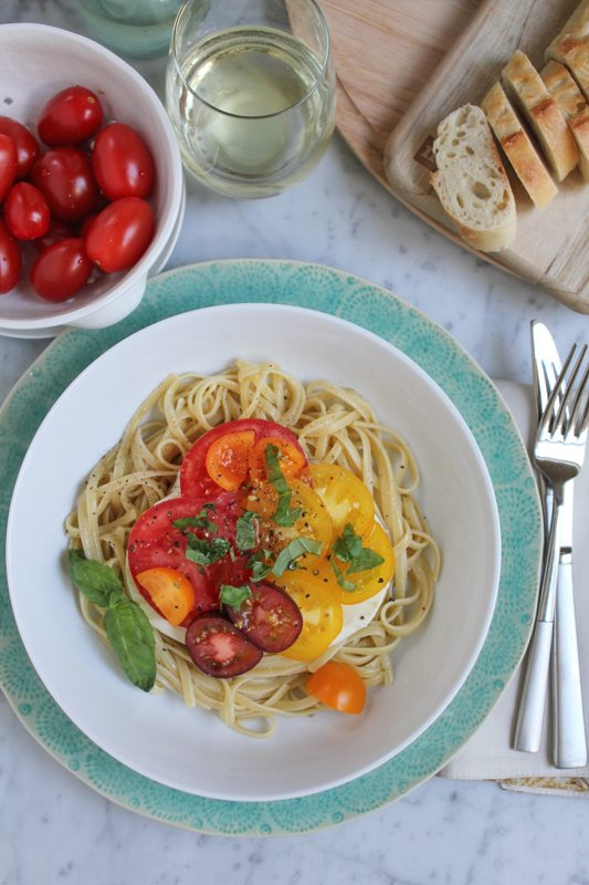 Summer Caprese pasta salad in a bowl with a small bowl of tomatoes, a glass of white wine, a wooden board with sliced bread, and silverware.