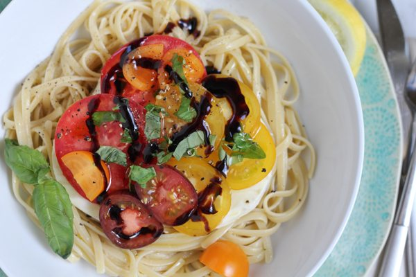 A bowl of Summer Caprese pasta salad drizzled with balsamic vinegar.