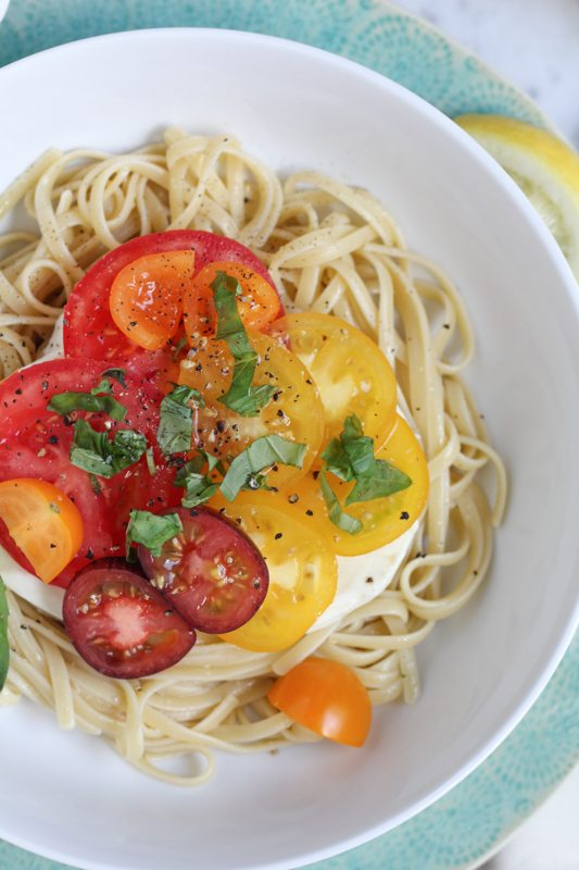 Summer Caprese pasta salad in a white bowl.