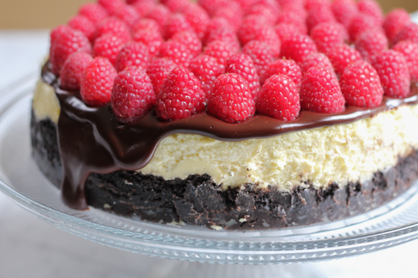 Rich, raspberry cheesecake with Oreo cookie crust and topped with a delicious chocolate ganache and topped with fresh raspberries. Doesn't get any better than this! #cheesecake