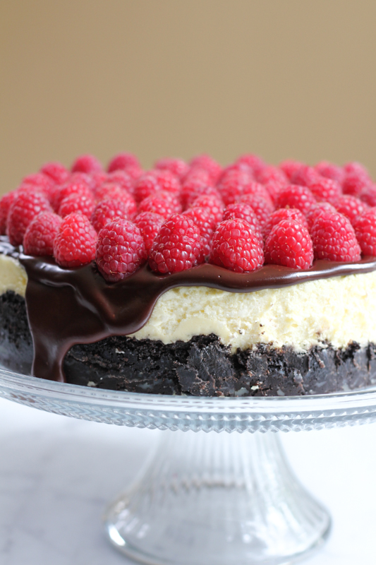 Rich, raspberry flavored cheesecake with an Oreo cookie crust and topped with a delicious chocolate ganache and topped with fresh raspberries. Doesn't get any better than this! #cheesecake