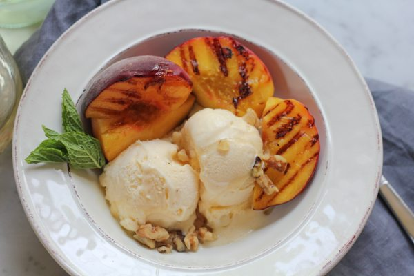 Vanilla ice cream with grilled peaches in a white bowl garnished with mint leaves.