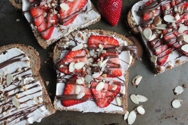 The Best Toast You'll Ever Have!! Toasted bread smothered with honey mascarpone & topped with fresh strawberries, melted Nutella and sliced almonds and hazelnuts.