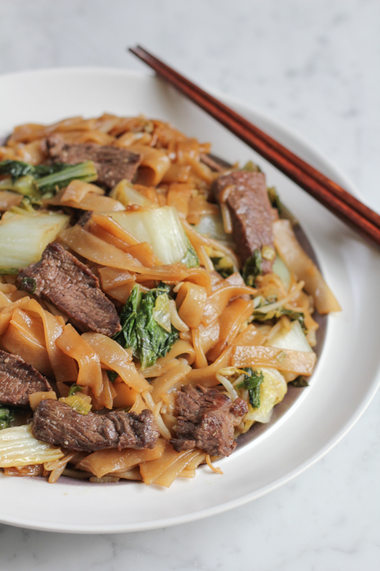 Beef Chow Fun! A staple Cantonese dish, made from stir-frying beef, wide rice noodles and vegetables, this delicious Chinese Food dish will come together in no time at all! Skip the take out and try cooking Chinese food at home!