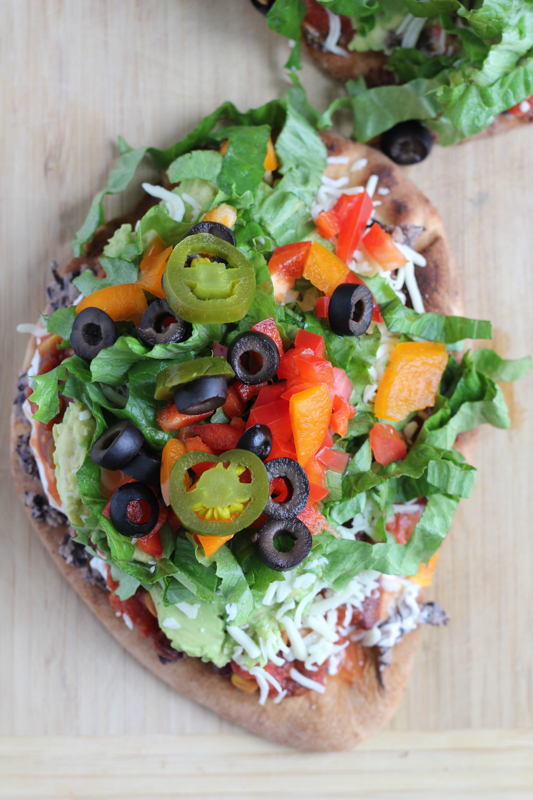 7 Layer Dip Flatbread! No more community bowl of 7 layer dip! Have your own on flatbread! It's so easy to make! #appetizer #gamedayfood #superbowl #quickrecipe