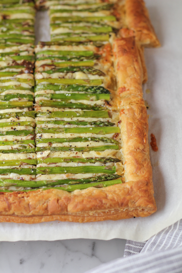 Sliced Asparagus Gruyere tart on parchment paper with a napkin.