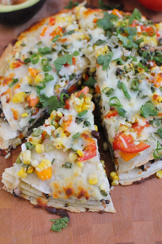 Sliced Corn and Black Bean Tortilla Tart on a wood cutting board.