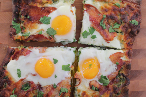 Grilled Breakfast Pizza with pesto. Fire up the grill and throw breakfast on the barbie!! You might never want just plain bacon and eggs again. #pizza #grilledpizza #grilling #breakfast