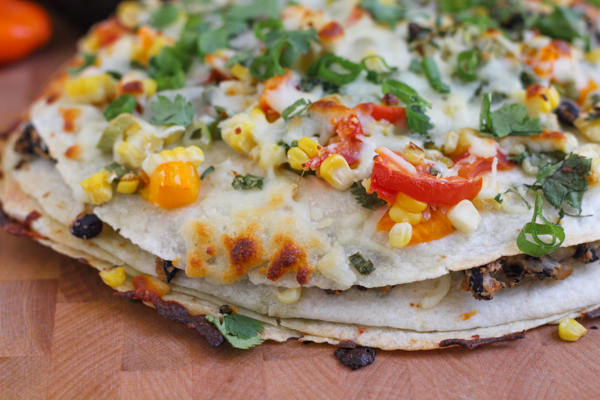 Change up Taco Tuesdays with this Corn and Black Bean Tortilla Tart! Simple, savory and so flavorful, it's like a baked Mexican pizza! Delicious! #Mexicanfood