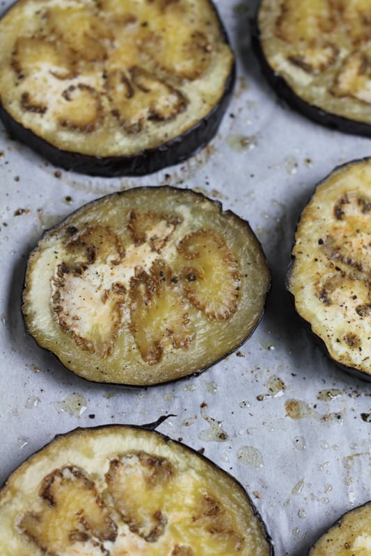 Slices of eggplant on a baking tray for Grilled Eggplant Bun Burger.