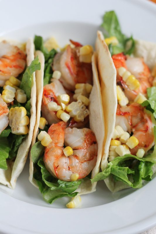Grilled Shrimp Tacos with Mexican Crema topped with grilled corn on a white plate.