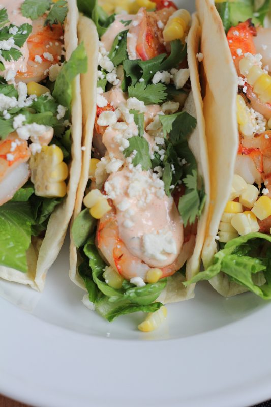 Grilled Shrimp Tacos with Mexican Crema topped with grilled corn, cilantro, and cheese, on a white plate.