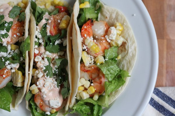 Grilled Shrimp Tacos with Mexican Crema on a white plate on a wood surface.