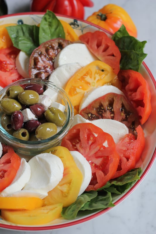 A platter of Simple Caprese Salad with a bowl of olives and feta in the center.