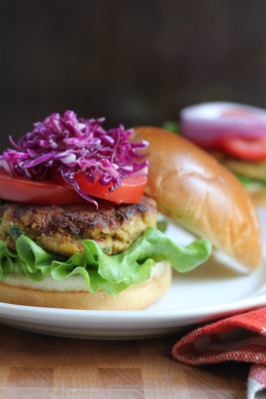 A chickpea burger topped with red cabbage slaw and tomatoes on a plate.
