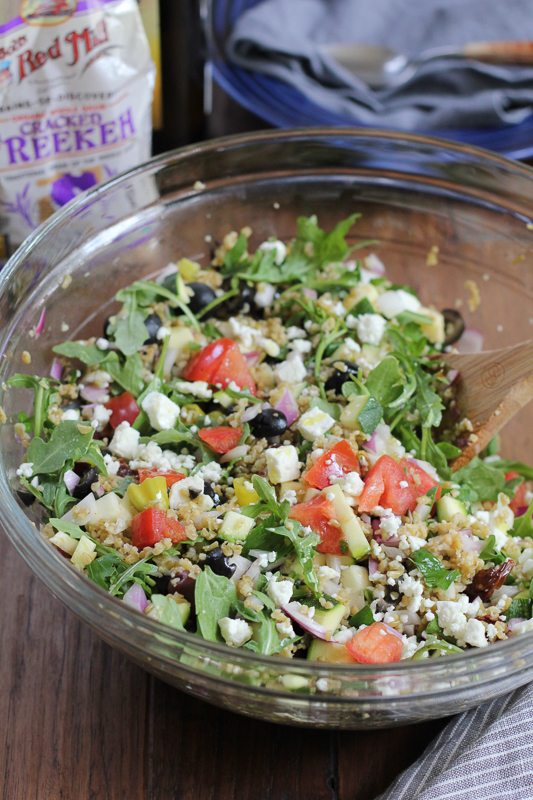 A glass bowl of Mediterranean Freekeh Salad.
