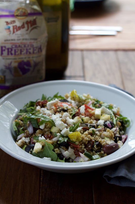 A bowl of Mediterranean Freekeh Salad with a bag of freekeh grains and olive oil in the background.