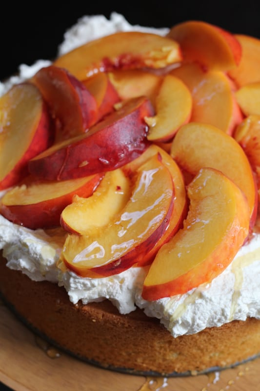 Close up photo of Olive Oil Honey Cake With Fresh Peaches on a wooden cake stand.