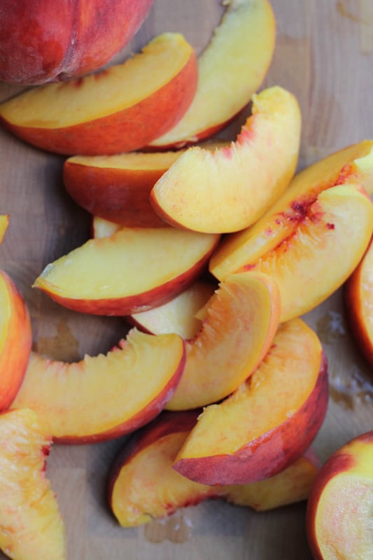 Sliced peaches for Olive Oil Honey Cake With Fresh Peaches.