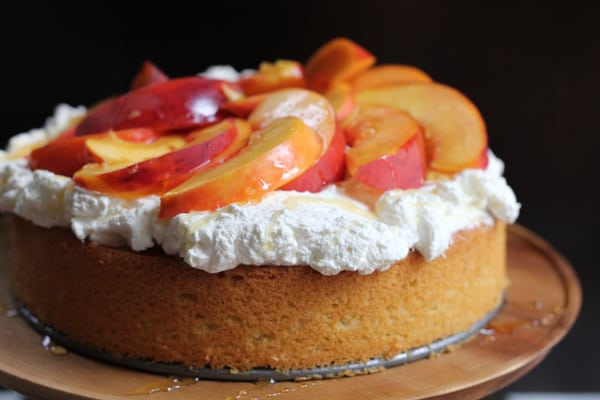 Olive Oil Honey Cake With Fresh Peaches on a wooden cake stand.