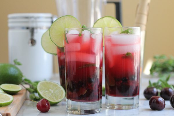 Glasses of Blueberry Cherry Mojitos with limes, cherries, and mint.