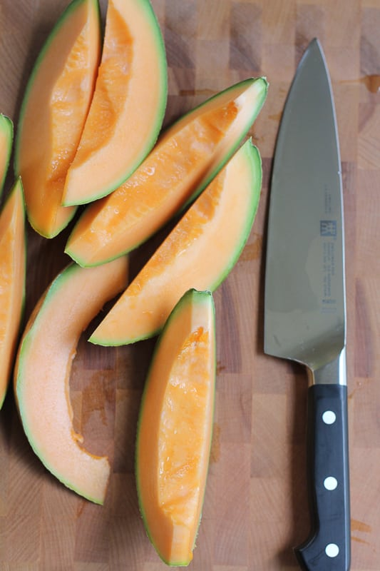 Slices of cantaloupe for Simple Cantaloupe Salad next to a knife.