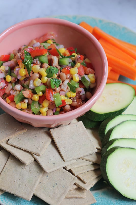 A bowl of Texas Caviar with sliced raw vegetables and crackers.