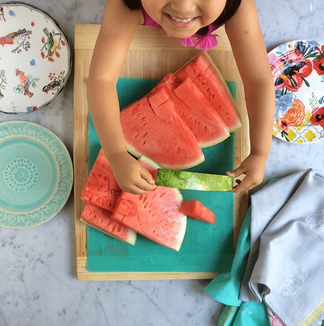 A child holding a slice of watermelon over sliced watermelon on a cutting board.