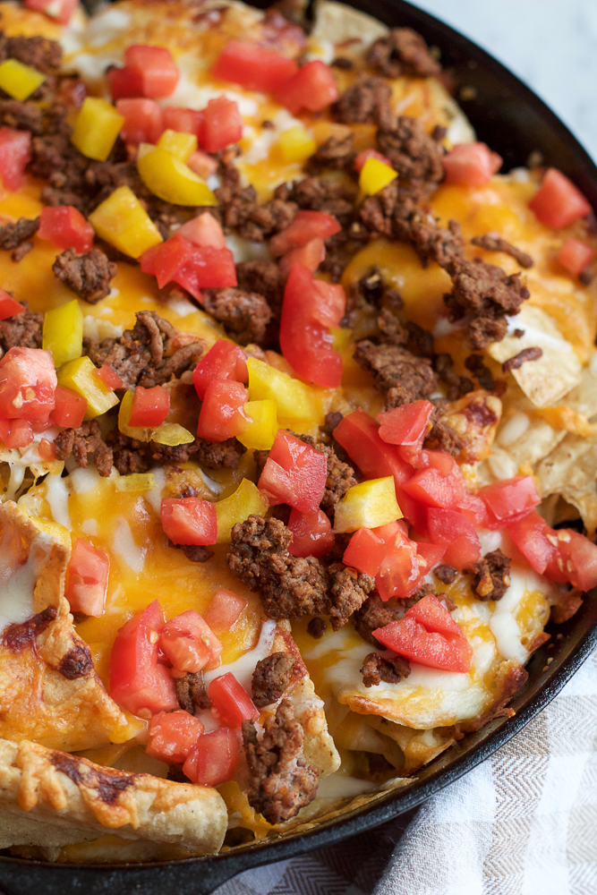 Skillet Nachos! Loaded with seasoned lean ground beef, cheddar cheese, mozzarella cheese, tomatoes, avocados, sour cream and salsa. You need this at your Super Bowl Party!