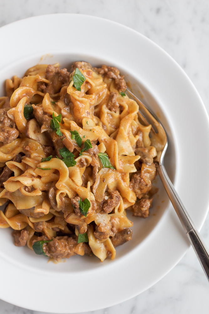 A bowl of One Pot Beef Stroganoff with a fork.