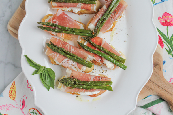 Roasted Asparagus and Prosciutto Crostini + A Video! Rich, creamy fresh ricotta cheese spread on toasted bread, topped with prosciutto and roasted asparagus. So EASY and makes an absolutely delicious appetizer!