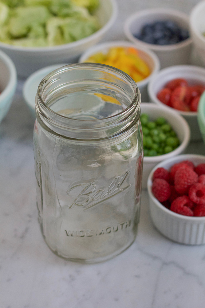 An empty mason jar for Mason Jar Salad with ingredients in bowls in the background.