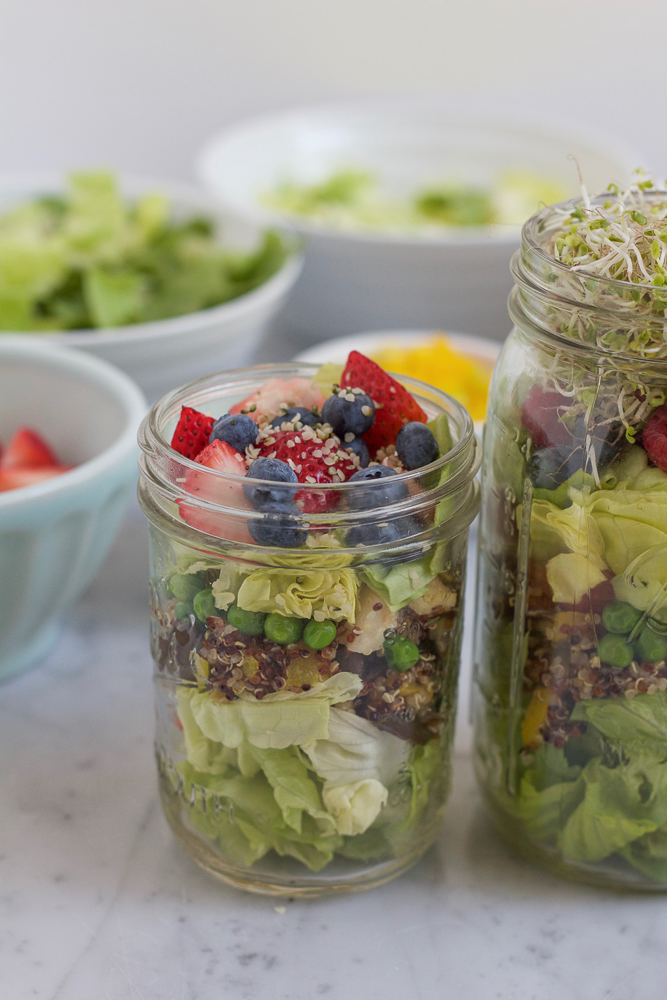 A small jar of Mason Jar Salad with ingredients in bowls in the background.