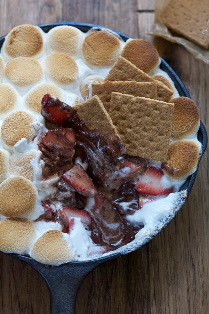 Easy S'mores Dip in a skillet, with graham crackers dipped in.