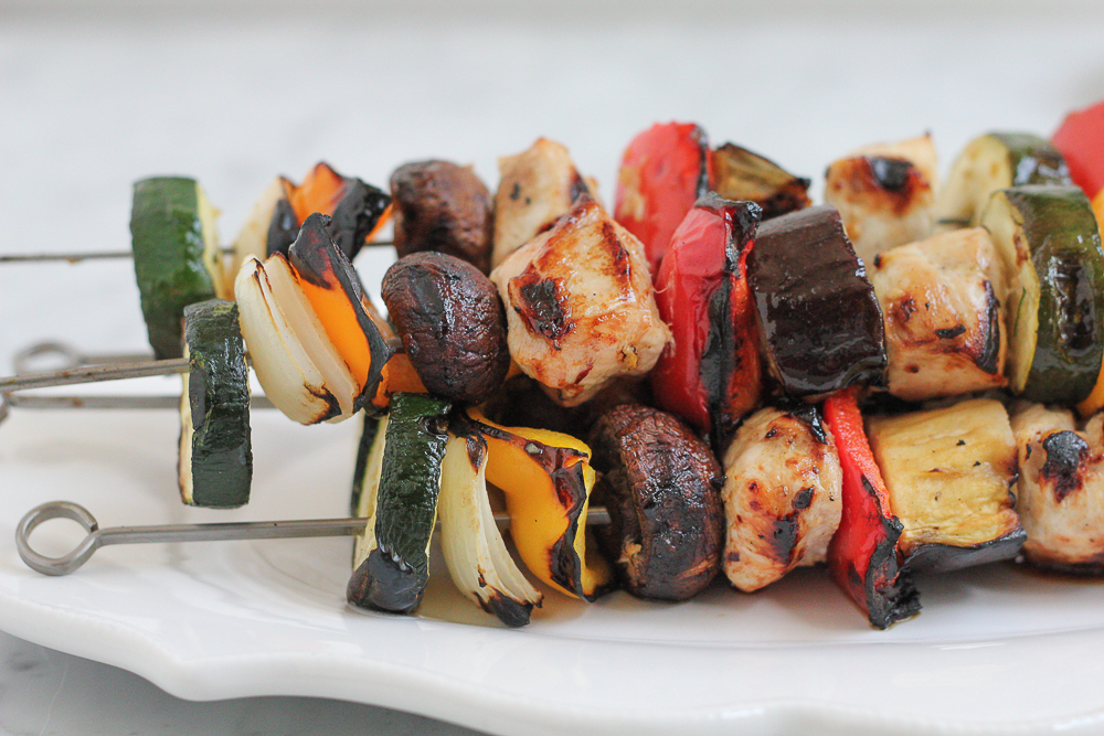 A stack of Grilled Chicken Kebabs on a white platter.
