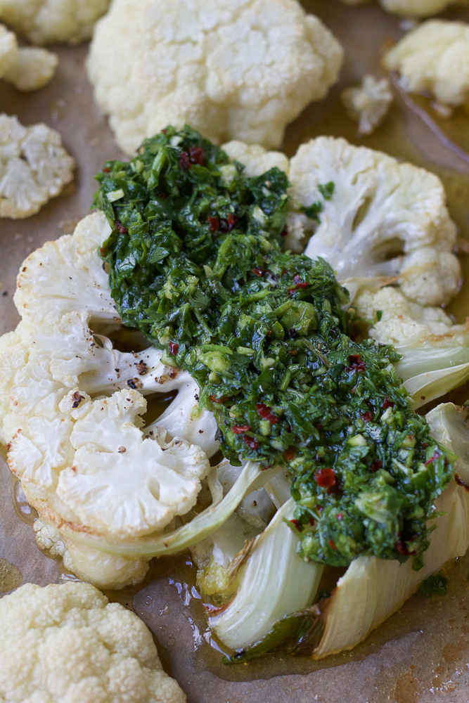 Grilled Cauliflower Steaks topped with chimichurri sauce.