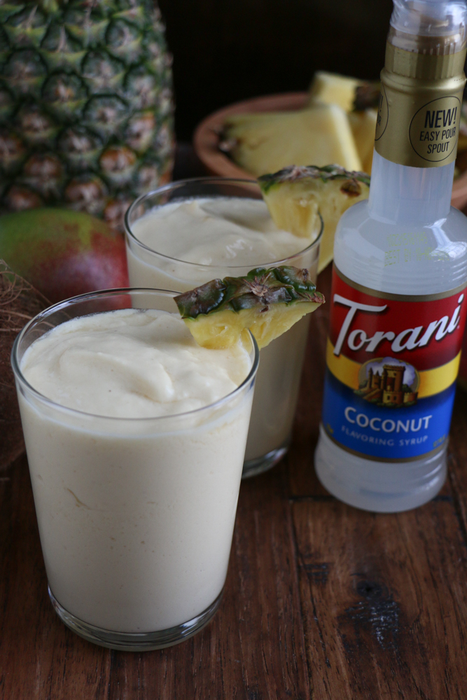 Two glasses of Refreshing Tropical Coconut Smoothie with a pineapple, mangos, and bottle of coconut syrup.