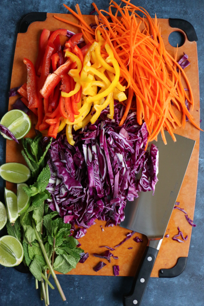 A board of chopped veggies for Chicken and Veggie Spring Rolls.