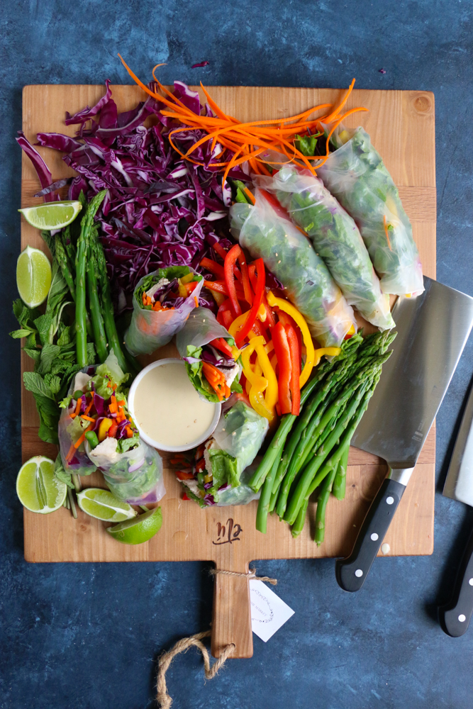A board of chopped vegetables, Chicken and Veggie Spring Rolls, a bowl of dipping sauce, and a knife.