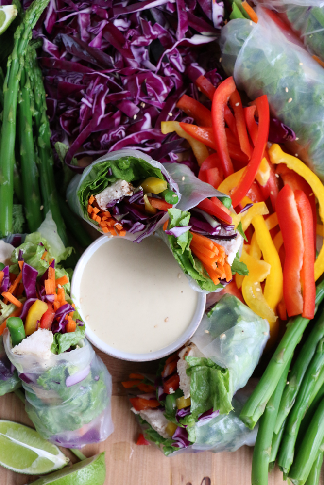 Chopped vegetables, Chicken and Veggie Spring Rolls and a bowl of dipping sauce on a board.
