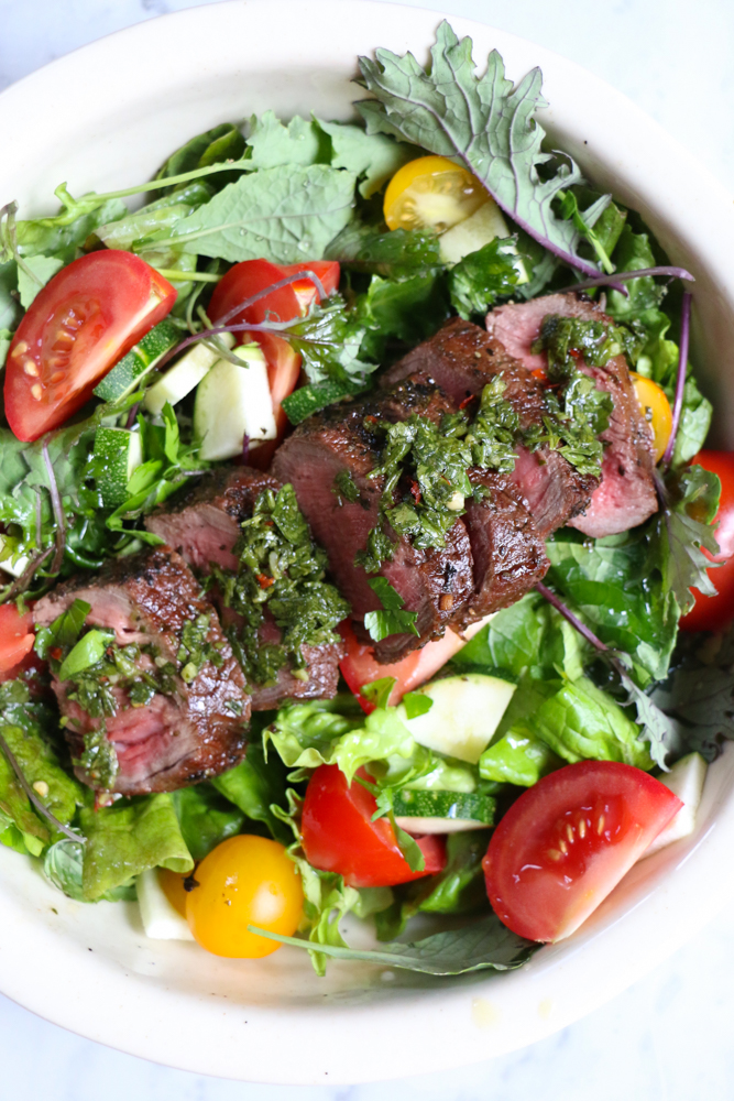 Overhead photo of a bowl of salad topped with sliced grilled steak made with steak marinade.