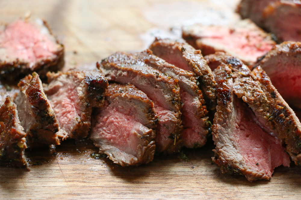 Sliced grilled steak on a wooden cutting board.