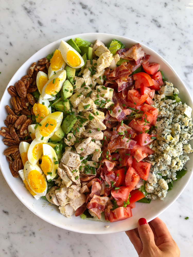 Best Cobb Salad ever! I use a homemade roast chicken, thick cut bacon, jammy eggs, tomatoes, blue cheese, romaine lettuce and more! So good!