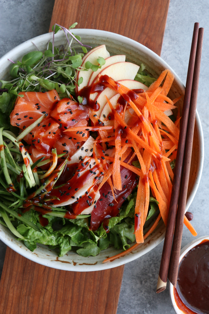 Sashimi Salad Bowl! Sliced sashimi over a bed of lettuce with fresh cucumbers, carrots, thinly sliced apples, micro greens and topped with a spicy gochujang sauce! So fresh and delicious!